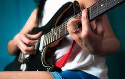 Junge Frau, die auf Gitarre spielt Abschluss oben Lizenzfreie Stockfotos