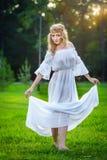 Junge Frau, die auf grünem frischem Gras in einem Park steht Stockbilder