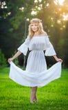 Junge Frau, die auf grünem frischem Gras in einem Park steht Lizenzfreies Stockfoto