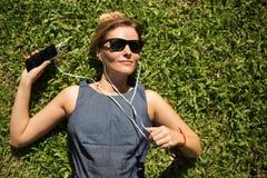 Junge Frau, die auf grünem Gras und hörender Musik liegt Stockfotografie
