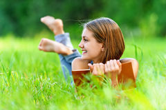 Junge Frau, die auf Gras liegt Stockfotografie