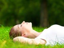 Junge Frau, die auf Gras liegt Lizenzfreie Stockfotos