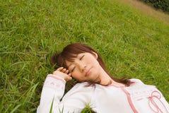 Junge Frau, die auf Gras schläft Stockbild