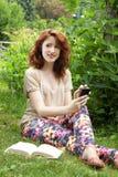 Junge Frau, die auf Gras sitzt Stockfotos