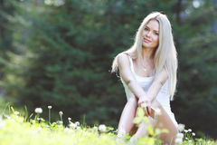 Junge Frau, die auf Gras sitzt Stockbilder