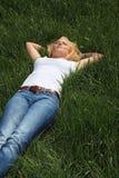 Junge Frau, die auf grüner Wiese ein Schlaefchen hält Stockfoto