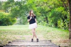 Junge Frau, die auf hölzerne Brücke geht Stockfoto
