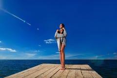 Junge Frau, die auf hölzernem Pier steht Stockfotografie