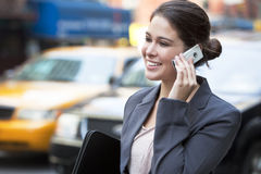 Junge Frau, die auf Handy durch gelbes Rollen spricht Lizenzfreies Stockbild