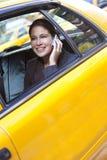 Junge Frau, die auf Handy im gelben Rollen spricht Stockbild