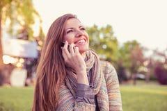 Junge Frau, die auf Handy spricht Zufälliges schönes Mädchen, das lächelnde glückliche Außenseite des Smartphone in einem Park ve stockbilder