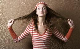 Junge Frau, die auf ihr langes Haar zieht stockbilder