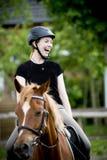 Junge Frau, die auf ihrem Pferd lacht Lizenzfreies Stockbild