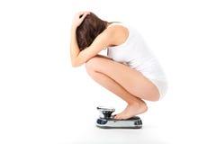 Junge Frau, die auf ihren Hinterteilen auf einer Skala sitzt Stockbild