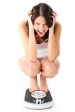 Junge Frau, die auf ihren Hinterteilen auf einer Skala sitzt Stockfoto