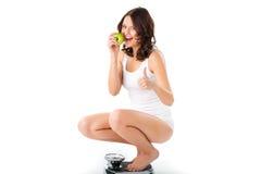 Junge Frau, die auf ihren Hinterteilen auf einer Skala sitzt Lizenzfreie Stockfotos