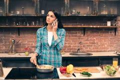 Junge Frau, die auf Küche kocht Lizenzfreies Stockbild