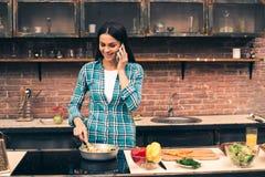 Junge Frau, die auf Küche kocht Stockbild
