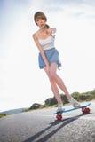 Junge Frau, die auf Kamera beim Balancieren auf ihrem Skateboard zeigt Stockbilder