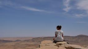Junge Frau, die auf Klippe ` s Rand sitzt und die Wüste betrachtet Stockbilder