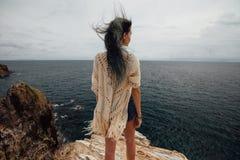 Junge Frau, die auf Klippe ` s Rand steht und eine breite Seeansicht untersucht Lizenzfreie Stockfotos