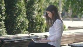 Junge Frau, die auf Laptop-Computer Tastatur beim Sitzen auf der Bank auf der Straße schreibt stock footage