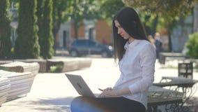Junge Frau, die auf Laptop-Computer Tastatur beim Sitzen auf der Bank auf der Straße schreibt stock video