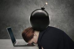 Junge Frau, die auf Laptop mit Bombe schläft stockfoto