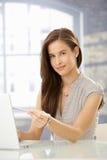 Junge Frau, die auf Laptopbildschirm zeigt Lizenzfreies Stockfoto