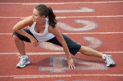Junge Frau, die auf laufende Spur ausdehnt Stockfotos