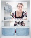 Junge Frau, die auf leerem Regal im Kühlraum schaut. Lizenzfreie Stockfotografie