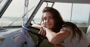 Junge Frau, die auf Lenkrad 4k sich lehnt stock footage
