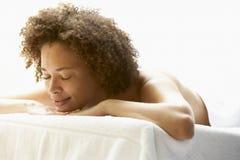 Junge Frau, die auf Massage-Tabelle sich entspannt Lizenzfreie Stockbilder