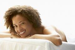 Junge Frau, die auf Massage-Tabelle sich entspannt Stockfoto