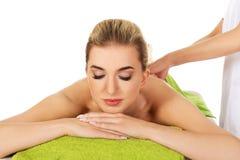 Junge Frau, die auf Massagetabelle liegt lizenzfreie stockfotos