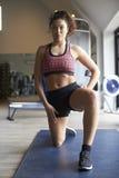 Junge Frau, die auf Mat In Gym trainiert Lizenzfreie Stockfotos