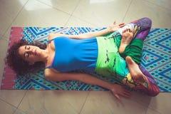 Junge Frau, die auf Matte mit den Beinen im Lotussitzinnenschuß liegt Stockfoto