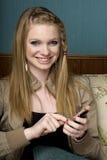 Junge Frau, die auf Mobiltelefon texting ist Stockfoto