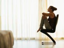 Junge Frau, die auf modernem Stuhl nahe Fenster sitzt Stockfotografie