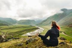 Junge Frau, die auf die Oberseite des Berges in der Meditations-Sitzung in Lotus Posture On Picturesque Summer-Berglandschafts-BA Lizenzfreies Stockbild