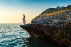 Junge Frau, die auf die Oberseite des Felsens steht und die Küste und den Sonnenuntergang in Sichang-Insel betrachtet Stockbild