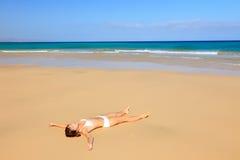 Junge Frau, die auf Ozeanstrand sich entspannt Lizenzfreie Stockfotos
