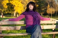 Junge Frau, die auf Park-Bank sitzt Lizenzfreies Stockfoto