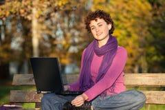 Junge Frau, die auf Park-Bank sitzt Lizenzfreie Stockfotos