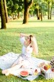 Junge Frau, die auf Plaid mit Früchten im Park sitzt lizenzfreie stockbilder