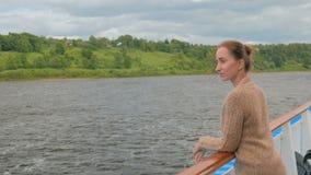 Junge Frau, die auf Plattform des Kreuzschiffs steht und Fluss und Landschaft betrachtet stock video footage