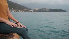 Junge Frau, die auf Plattform durch das Wasser, untersuchend Abstand sitzt stock footage