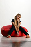 Junge Frau, die auf Puff sitzt Stockfoto
