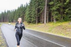 Junge Frau, die auf regnerischer Straße in den Bergen rüttelt Lizenzfreie Stockbilder