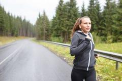 Junge Frau, die auf regnerischer Straße in den Bergen rüttelt Lizenzfreie Stockfotografie